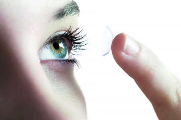 Contact lens use. Woman putting in a contact lens. --- Image by © Science Photo Library/Corbis